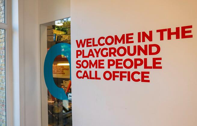 Quote op muur waar op staat 'Welcome in the playground some people call office' op kantoor bij Liquid Society in Brugge